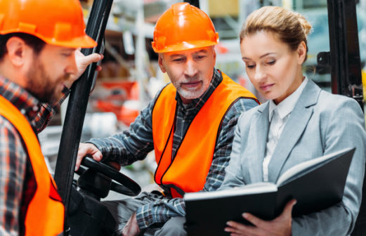 two workers and inspector using forklift machine in storehouse